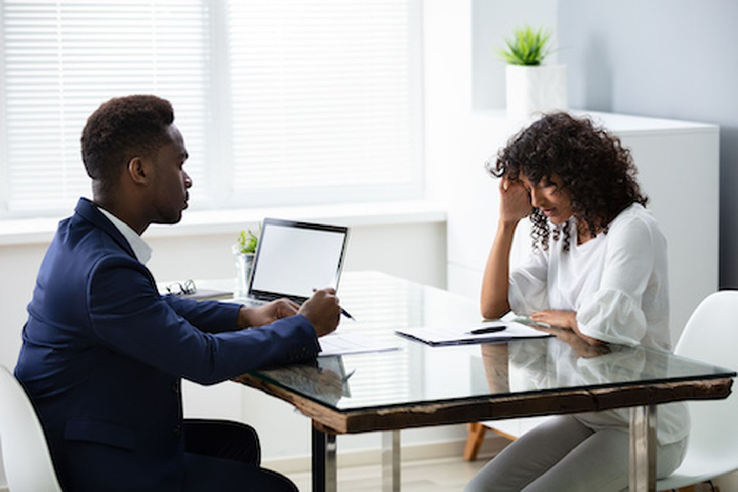 Stressed young business woman holding her head at interview