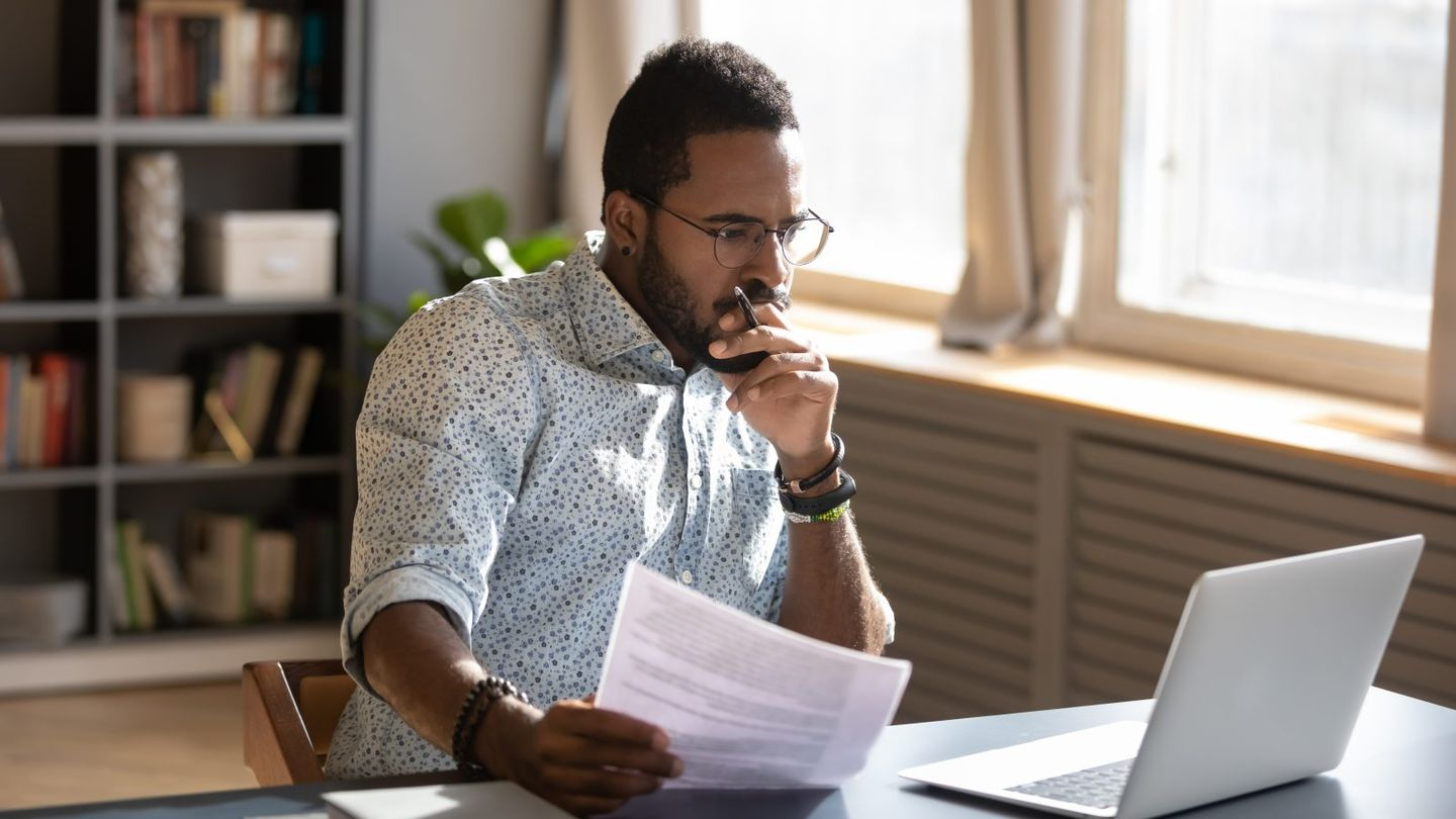 Focused african businessman holding documents looking at laptop doing research