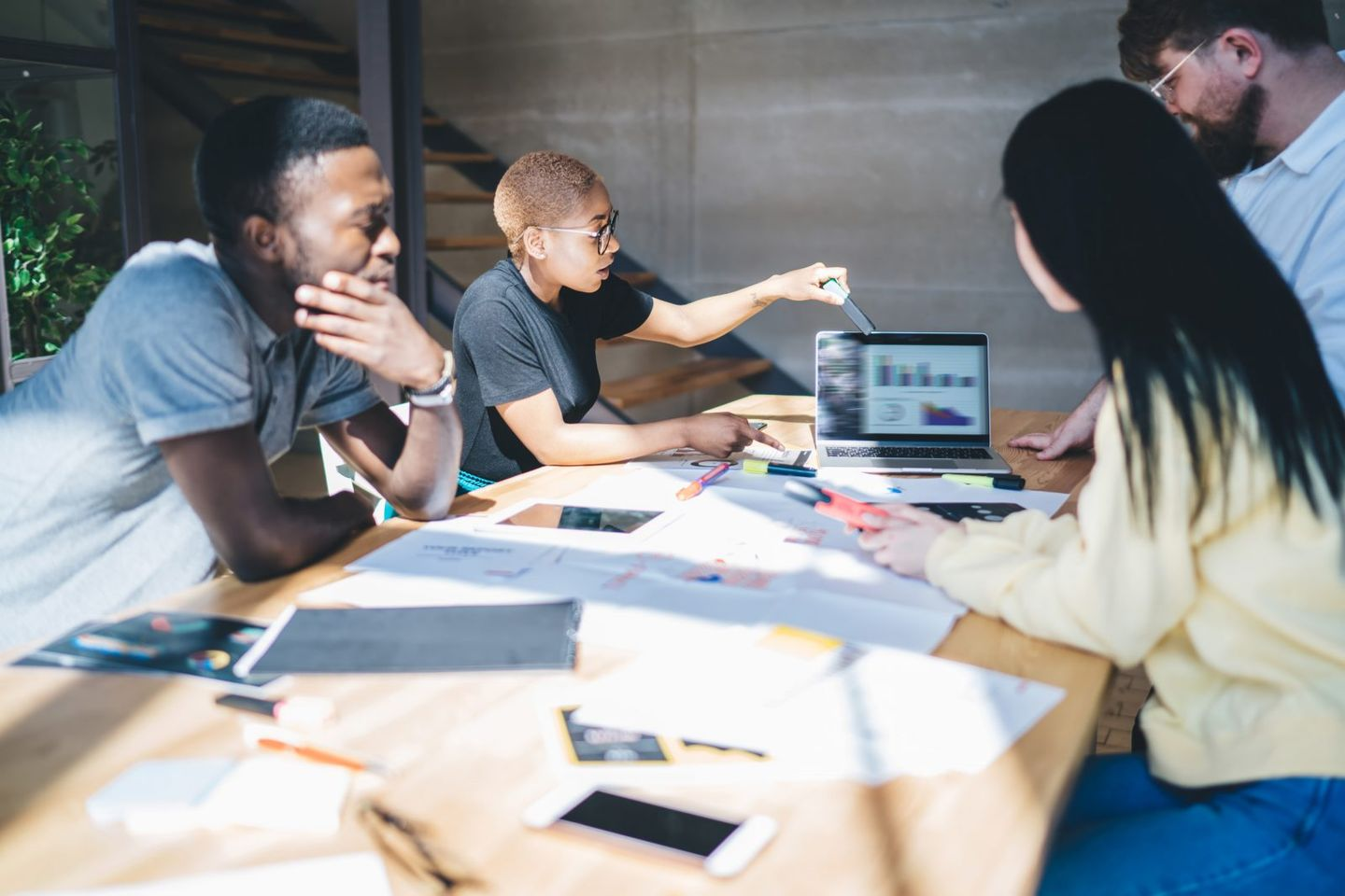 Black woman presenting charts on laptop during meeting with colleagues