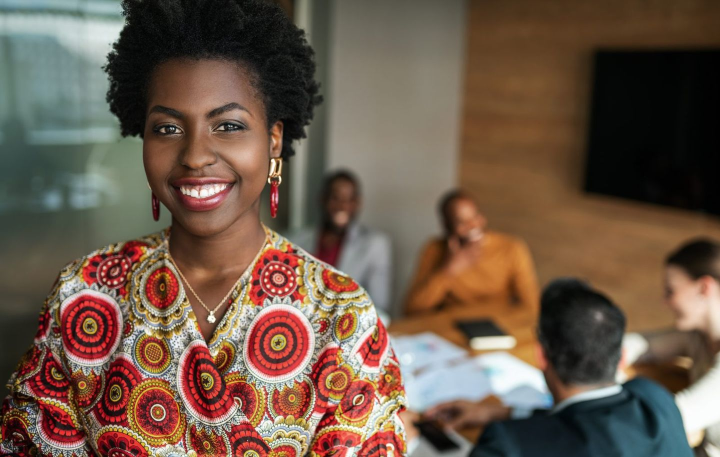 Close up of beautiful young smiling professional black african business woman coworkers hold a meeting in background