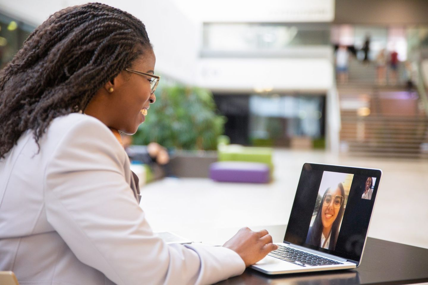 Happy female office friends talking through video call
