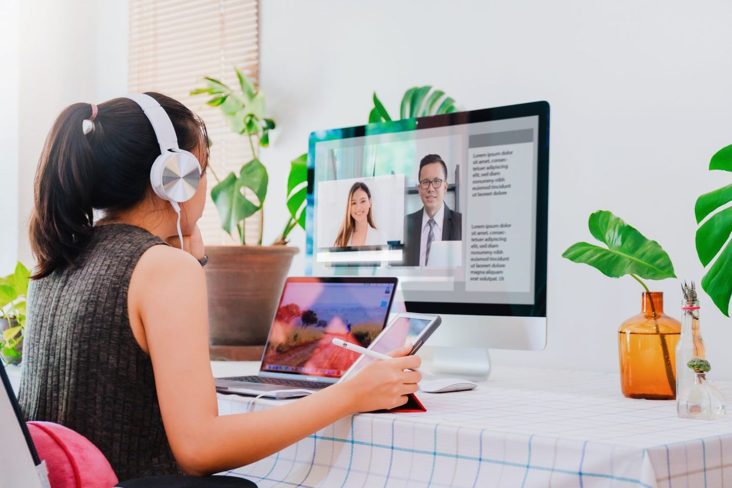 Asian business woman work from home with laptop tablet and computer on table with meeting online and video conferencing concept of social distancing to stop the spread disease of corona virus