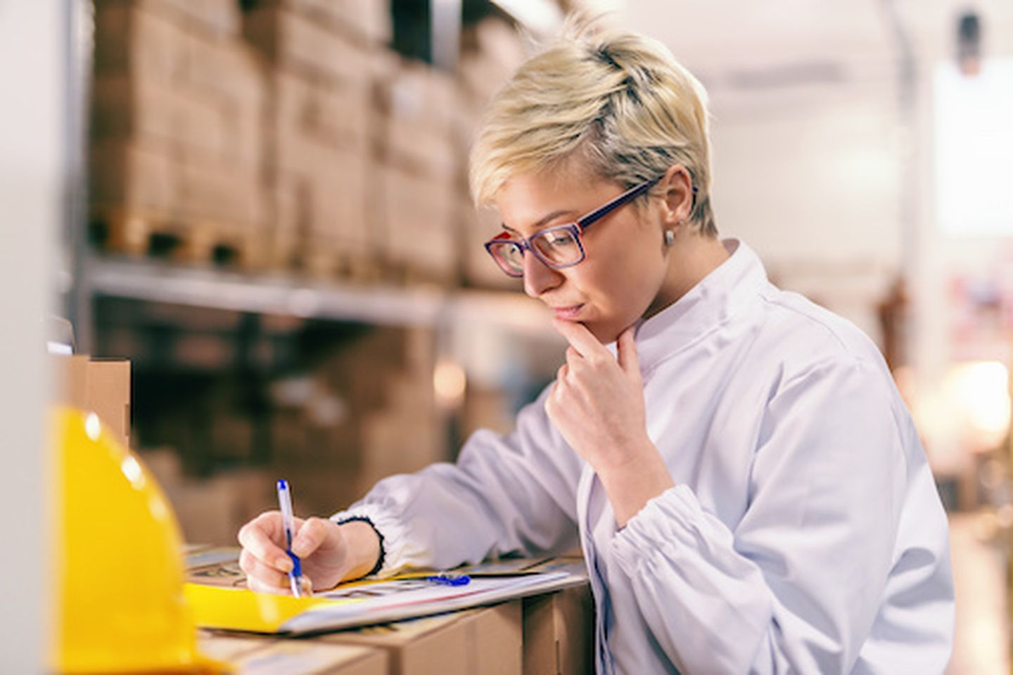 Young blonde caucasian woman in white uniform and with eyeglasses filling out paperwork while standing in warehouse