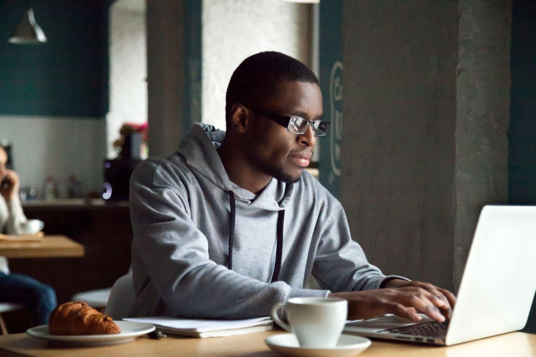 Serious millennial african american man using laptop sitting at