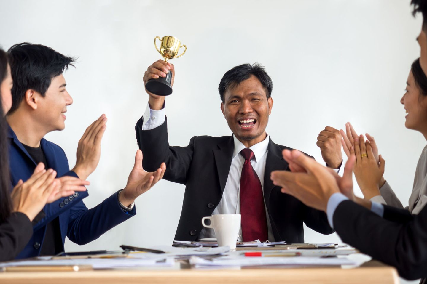 Businessman clapping hands with trophy reward winner champion and successful for business