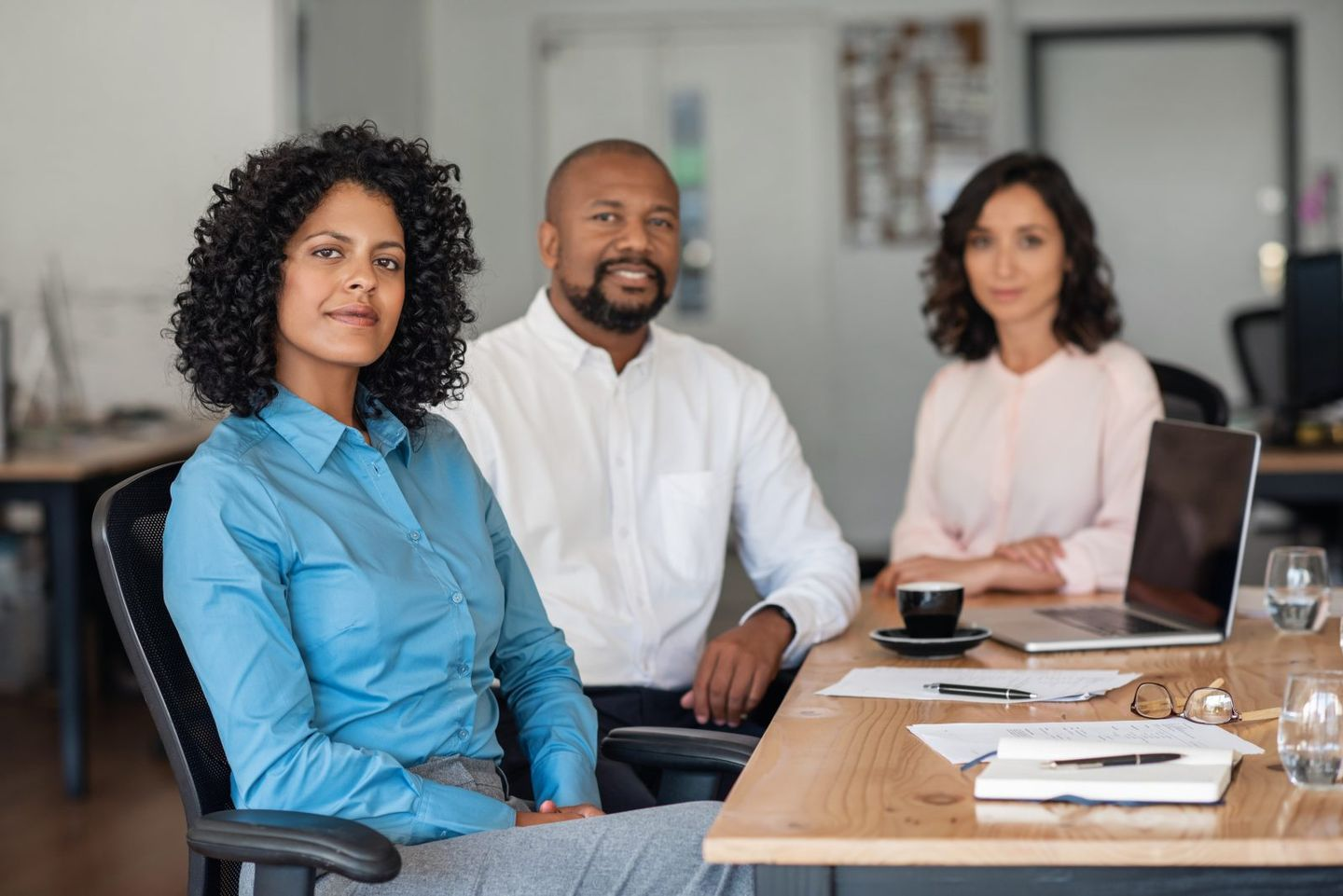 Employees sitting at board room table