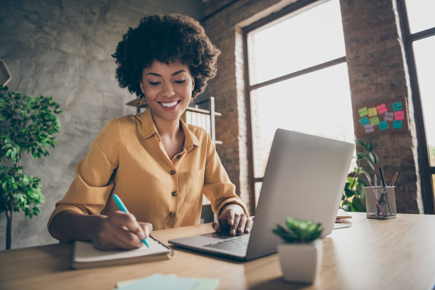 Photo of cheerful pretty cute nice girlfriend having been employed to job as executive smiling toothily sitting at desktop with laptop noting down important information