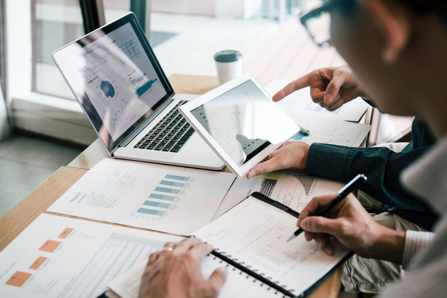 Business partnership coworkers using a tablet to analysis graph company financial budget report and cost work progress and planning for future in office room