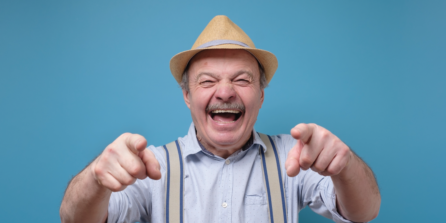 Older man pointing and laughing