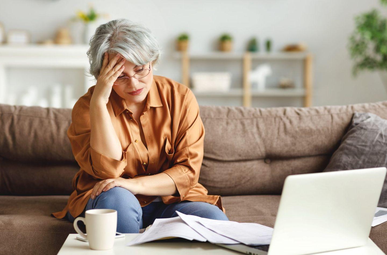 Stressed senior freelancer reading document 2