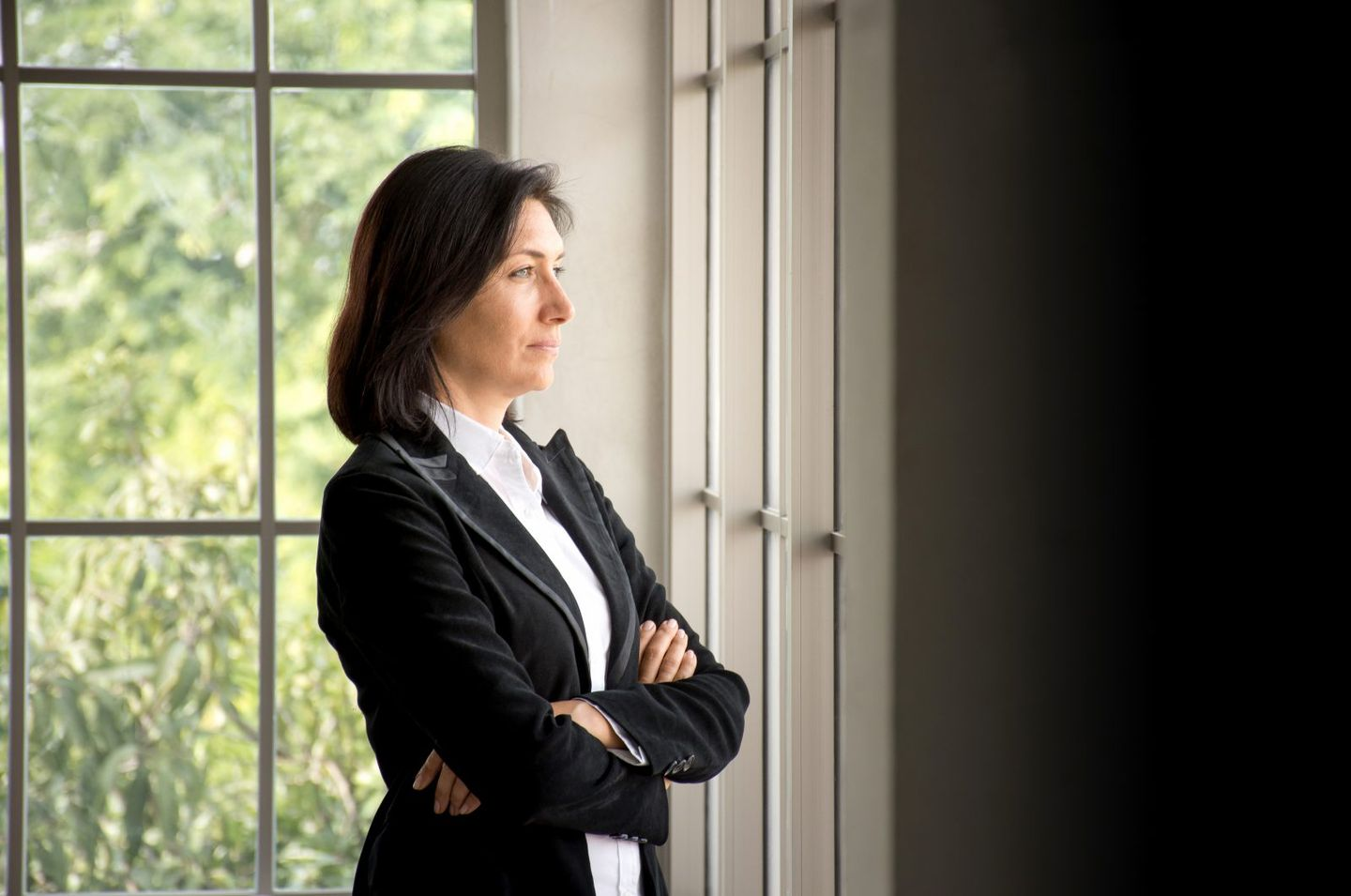 Portrait of confidence caucasian businesswoman crossed her arms and looking out the window
