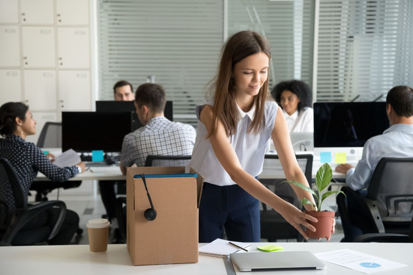 Smiling hired female company employee unpacking box with persona