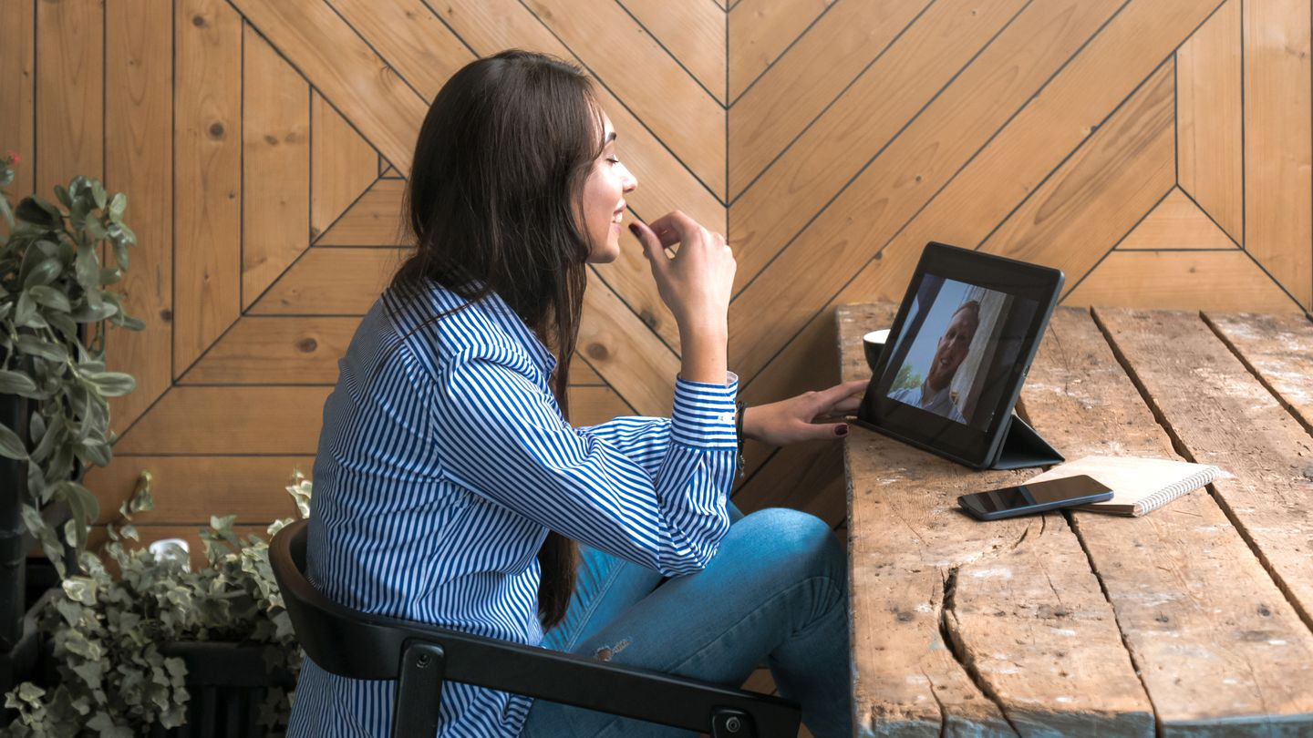 Beautiful cute caucasian young female with long black hair in rustic cafe having a video call with a friend