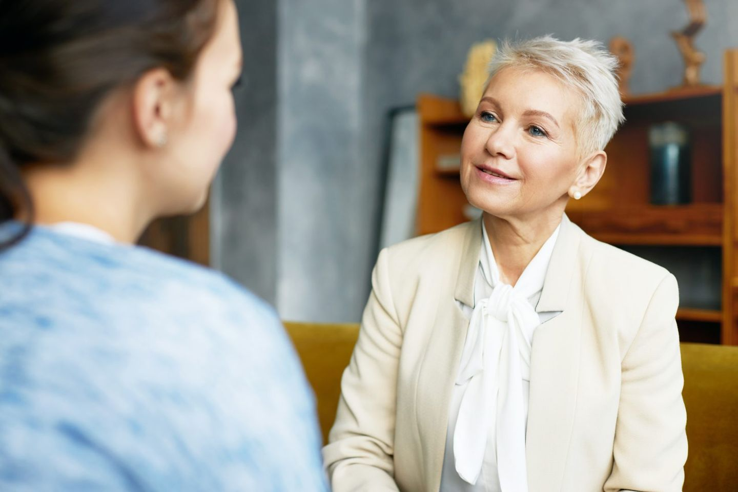 Psychology consulting and coaching concept stylish middle aged female psychologist having conversation with brunette woman client discussing problems and progress sitting in her cozy office