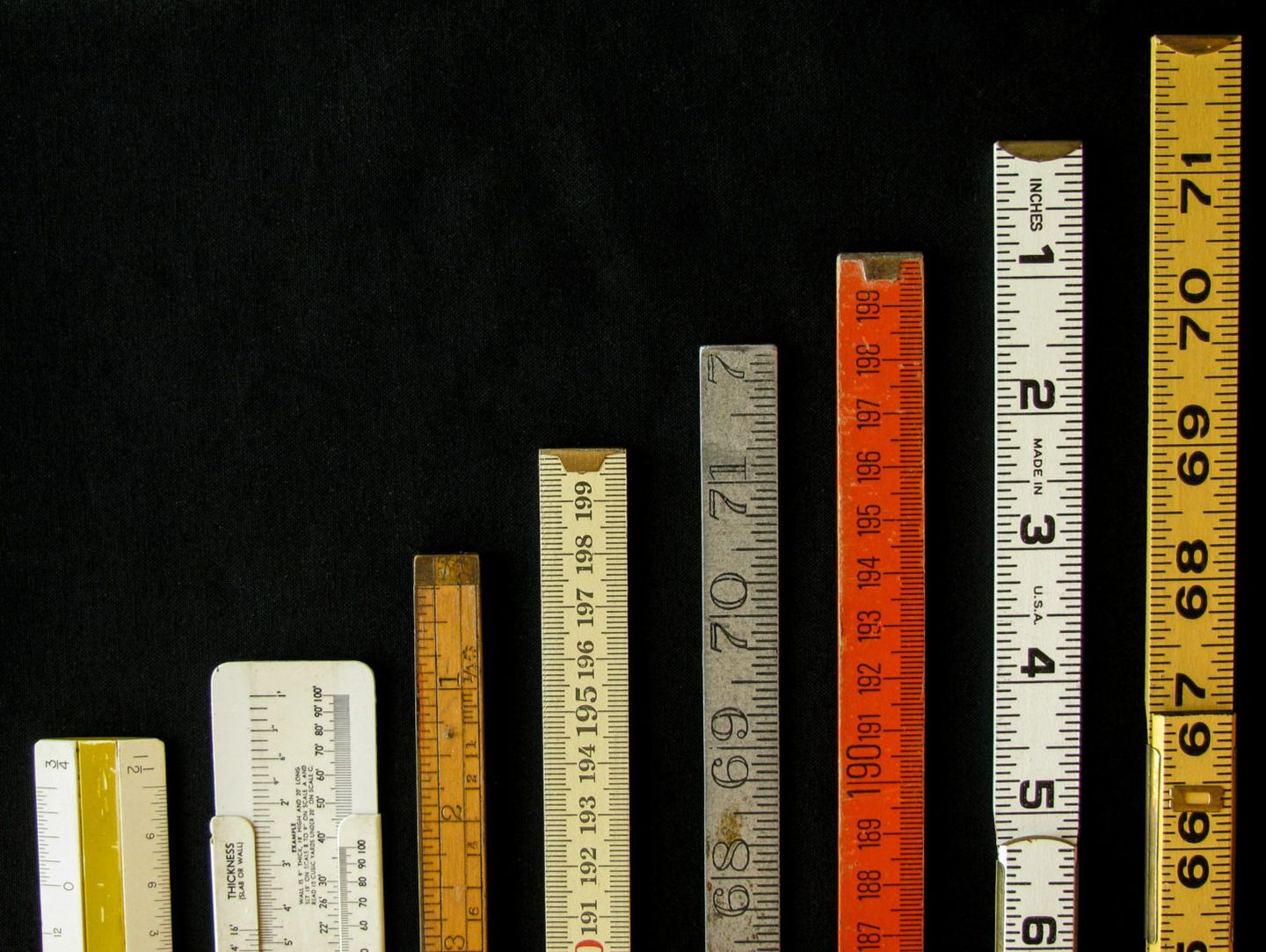 Rulers and scales in metric and inches ascend along a chart or graph representing measurement metrics precision increase growth accuracy and results with copy space