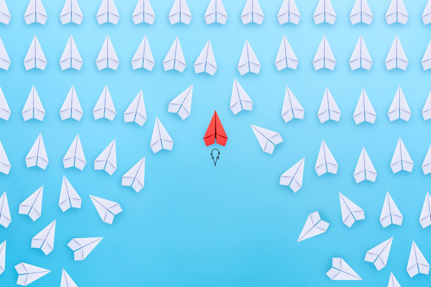 Business competition successful businessman concept with red paper plane flying overtake the other white paper planes on blue background