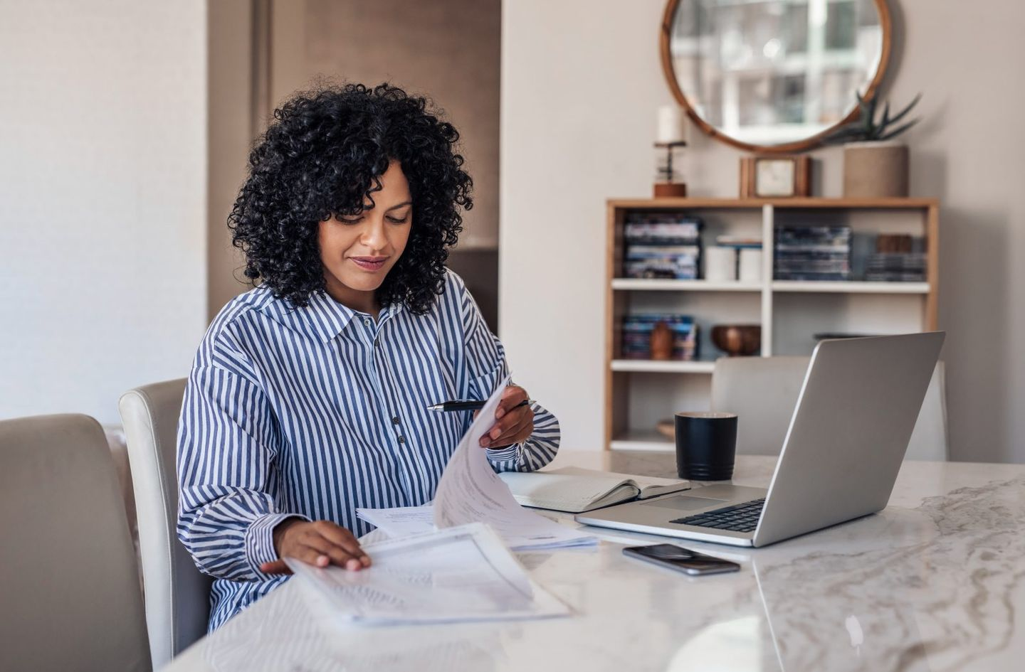 Smiling female entrepreneur going through paperwork at her dining table