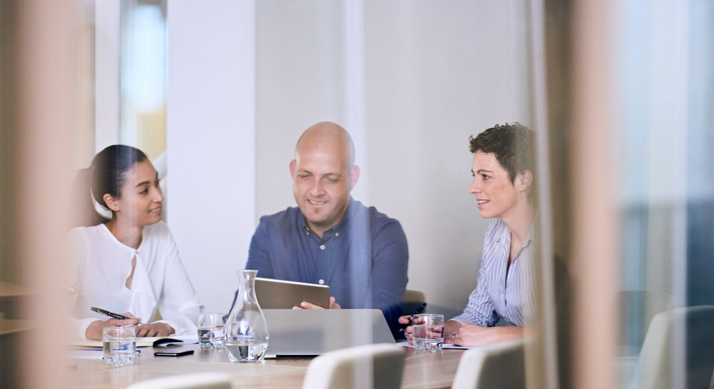 Business meeting in conference room with reflections on glass office