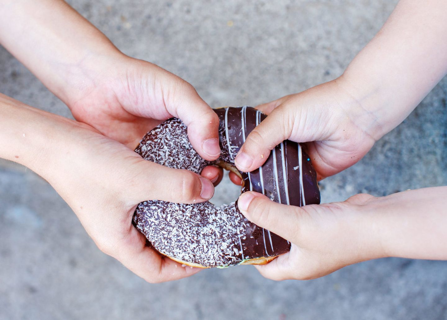 Childrens hands holding a chocolate donut two kids pull to themselves donut closeup the concept of sharing food