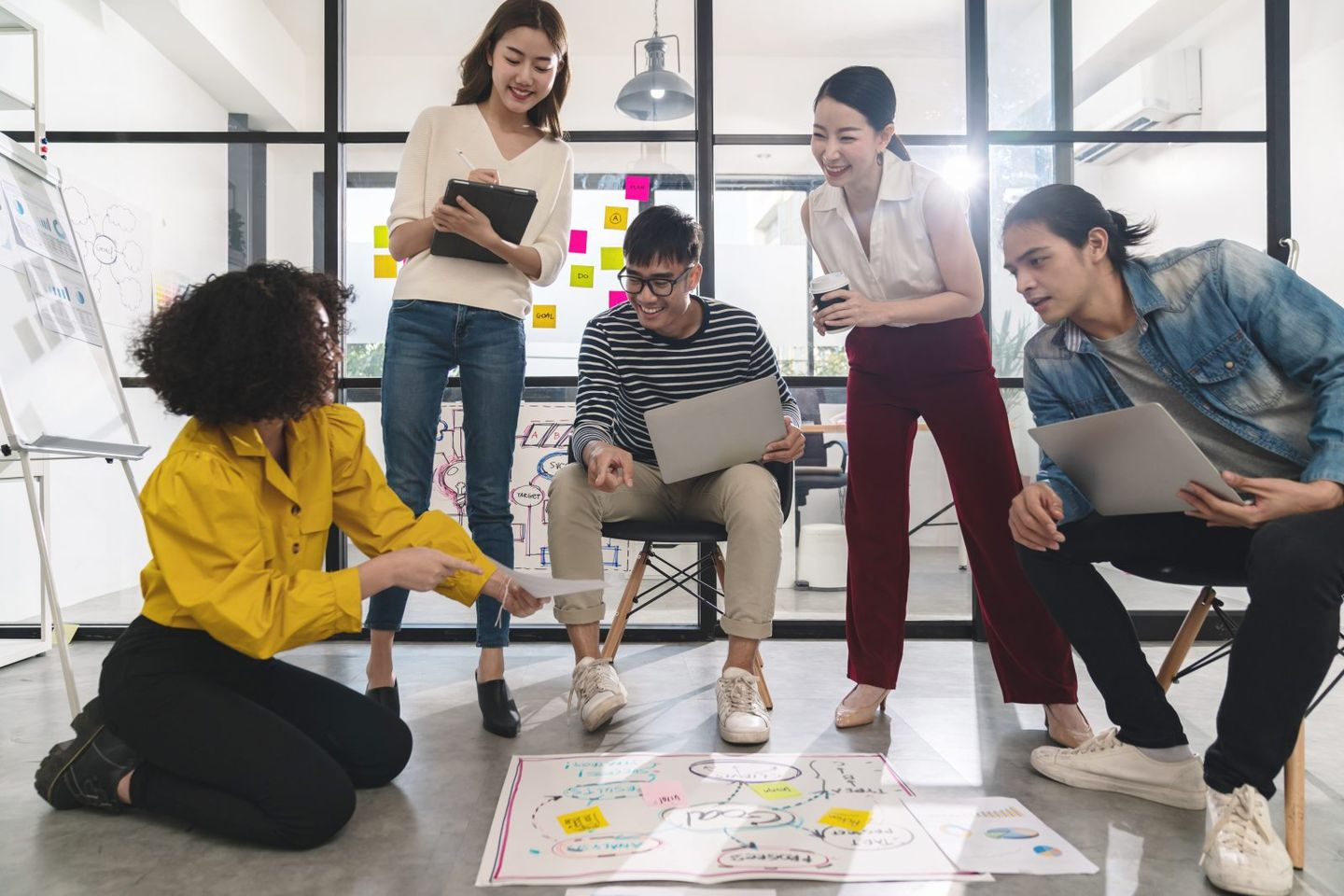 Young creative asian group meeting and looking at project plan lay out on floor discuss or brainstorm business strategy with post note workshop for startup team in small office happy workplace